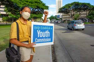 Staff writer Kiana Dulan participates in a sign-waving in support of establishing a Hawai'i Youth Commission.